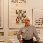 Old man in front of posters of Finnish architecture.