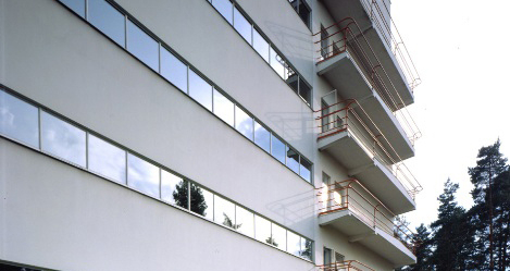 White office building with narrow window rows for each level.