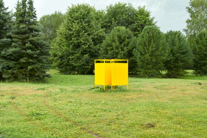 Yellow changing room in the middle of a lawn.