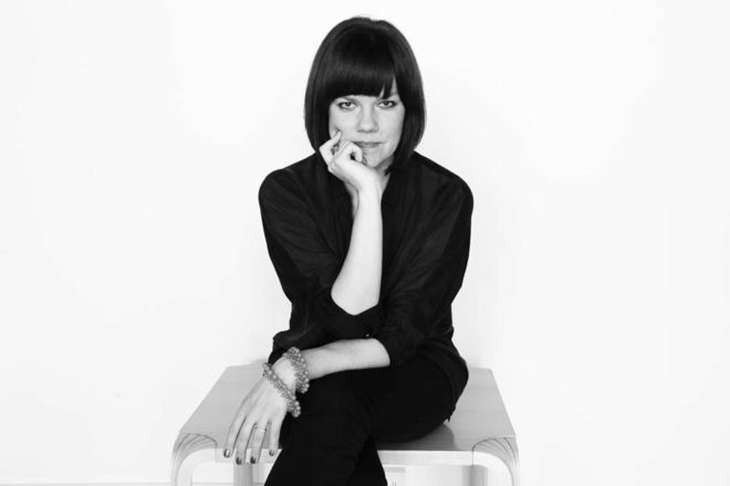 A black and white image of a woman with short black hair and black clothes