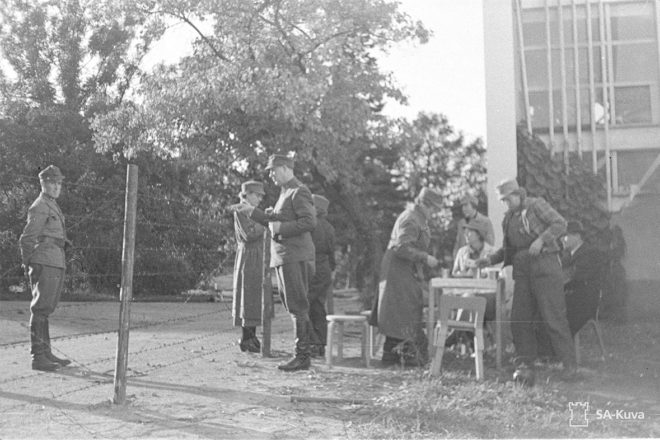 People in military suits are pouring coffee outside. The photo is in black and white.