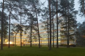 Paimio sanatorium at dusk. The lights of the sanatorium glow from behind pine trees.
