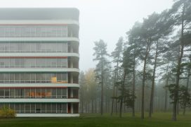 Paimio Sanitorium's façade with balconies. Next to the building a foggy pinewoods.