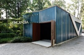 "Blue and white pavilion with a white triangle-like geometric shape on the side and white text ""Finlandia"" by the entrance."