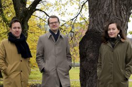 Curators standing in front of a tree at a park in autumn.