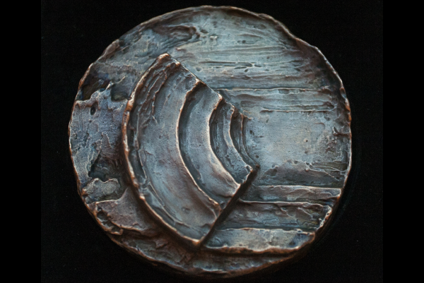 Round, grainy copper medal part of which are patinated blue. In the middle there is a amphitheatre-like shape.