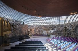 Temppeliaukio Church's hall: the strip windows that surround the border of the hall separate the copper dome ceiling from the bare rock walls. In the foreground, the church benches, on the left the organ. The view faces the altar.alanpalvelus sali: salin katon rajaa kiertävät nauhaikkunat erottavat kuparisen kupolikaton paljaista kalliokivisistä seinistä. Etualalla kirkon penkit, vasemmalla urut. Näkymä suuntautuu kohti alttaria.