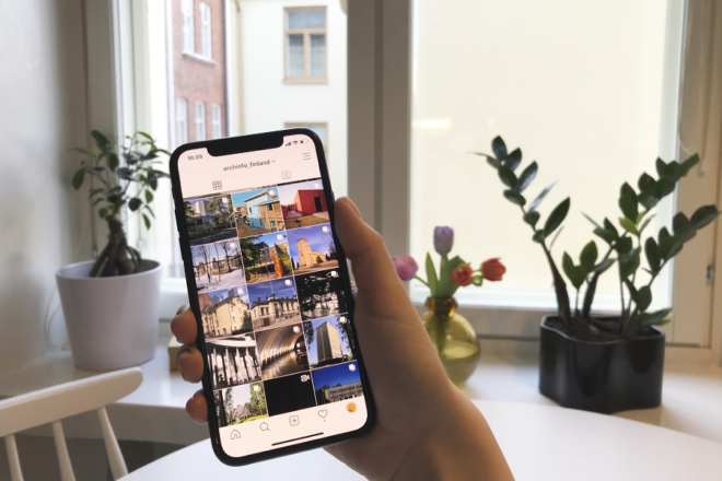 Someone is holding a phone, Archinfo Finland's Instagram account is open on the screen. On the background a window sill with plants and flowers.