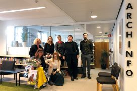 Archinfo Finland's seven employees smiling in the office foyer.