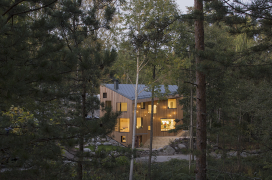 A wooden, sharp-angled and geometric three-storey house is visible in the middle of a coniferous forest. Warm light glows from the big windows.