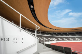 Wooden canopy curving over the stands. In the front, a white-rendered wall with section and row numbers.
