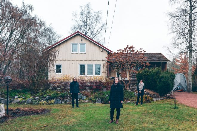 Yellow wooden house in a garden, three people standing in front of it in a triangular formation. Gray, cold-looking weather.