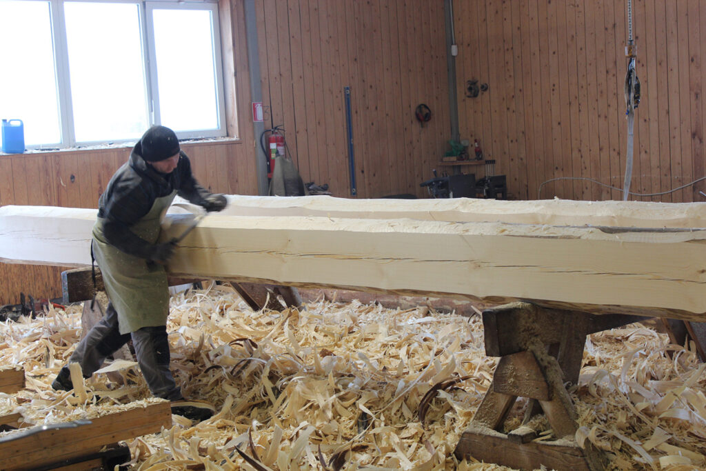 A man carves a big log in a workshop, the floor full of shavings.