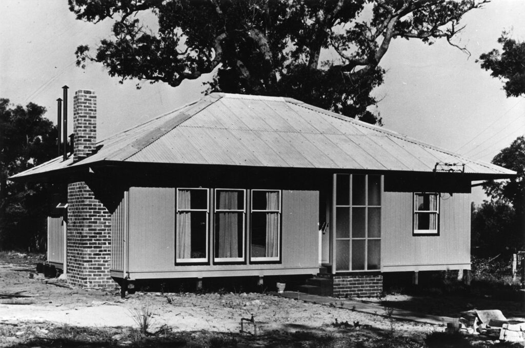 A black and white photo of a Puutalo Oy's wooden house. The eaves of the house are long, the windows are relatively large and on the side wall there is a chimney. In the background is a large and winding tree.