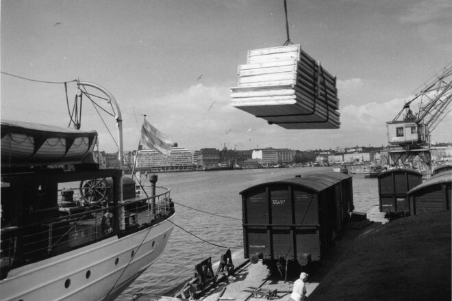 Black and white picture of panels manufactured in Puutalo corporation's factories being loaded on a ship in the South Harbour of Helsinki in the 1950s.