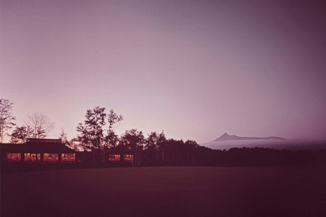 Golf Club in Japan, designed by Kaija and Heikki Siren, photographed at dusk. In the background is a mountain covered with a cloud of fog.