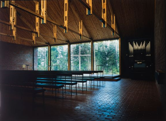 Interior of a chapel, wooden trusses and ceiling, brick floor and walls, full-width window with a view to a simple cross outside and forest