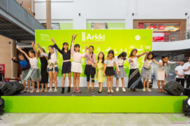 Children cheering on a stage decorated with Arkki's brand colours.