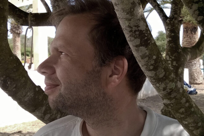 A close-up photo of a middle-aged man leaning against a tree, palm trees in the background
