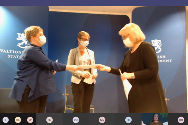 Screenshot from a Teams conference. Three ladies, one handing out a report to the two other ones, everyone wearing masks. Official Finnish government's backdrop.
