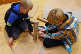 Two children sitting on the floor building something from cardboard and tape