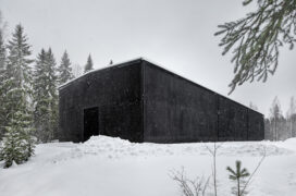 A black building in a wintery landscape. The building is surrounded by coniferous tree on the left.