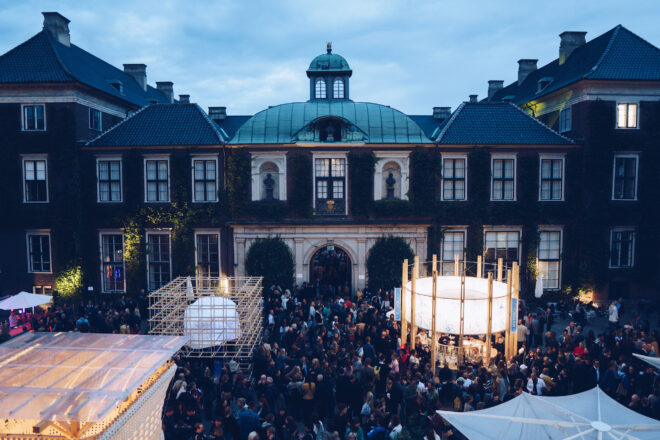 In front of a building, which consists of a few floors, there is a huge number of people. The evening is already getting dark, but the lights from the stalls in front of the buildings illuminate the surroundings.