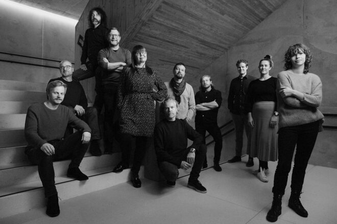 Black and white photo where the staff of K2S Architects poses for a camera in staircase.