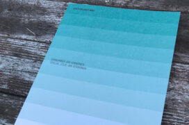Cover of a magazine with gradient hues of turquoise, laid on a wooden surface.