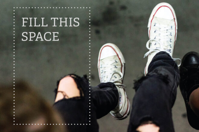 The legs of two different people depicted from above hang side by side in the air. The other person is wearing black, broken jeans and white sneakers. The other person is wearing blond, bare ankles and black sneakers. The background is blurry.