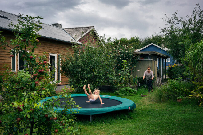 A child bouncing on a trampoline in a lush garden of a brownish wooden house. A woman pushing a lawnmower. A blue wooden house in the background