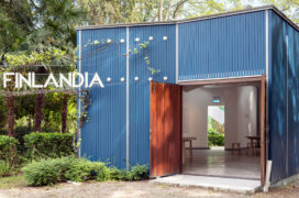 Blue wooden pavilion with letters FINLANDIA hanging outside. Open door, inside exhibition objects