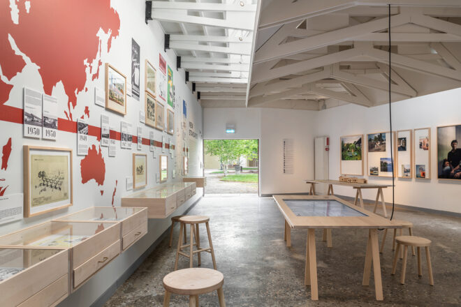 Inside the pavilion. On the left-side wall a world map in red, old images in frames. A wooden table with an incrusted screen in the middle. On the right side wall a series of photos.