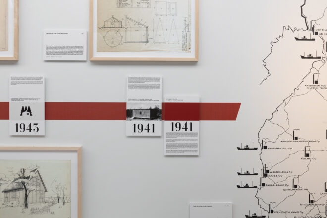 A view to detail of the exhibition, where there is a part of Finland's map and notes attached to the wall with years and information of Puutalo houses.