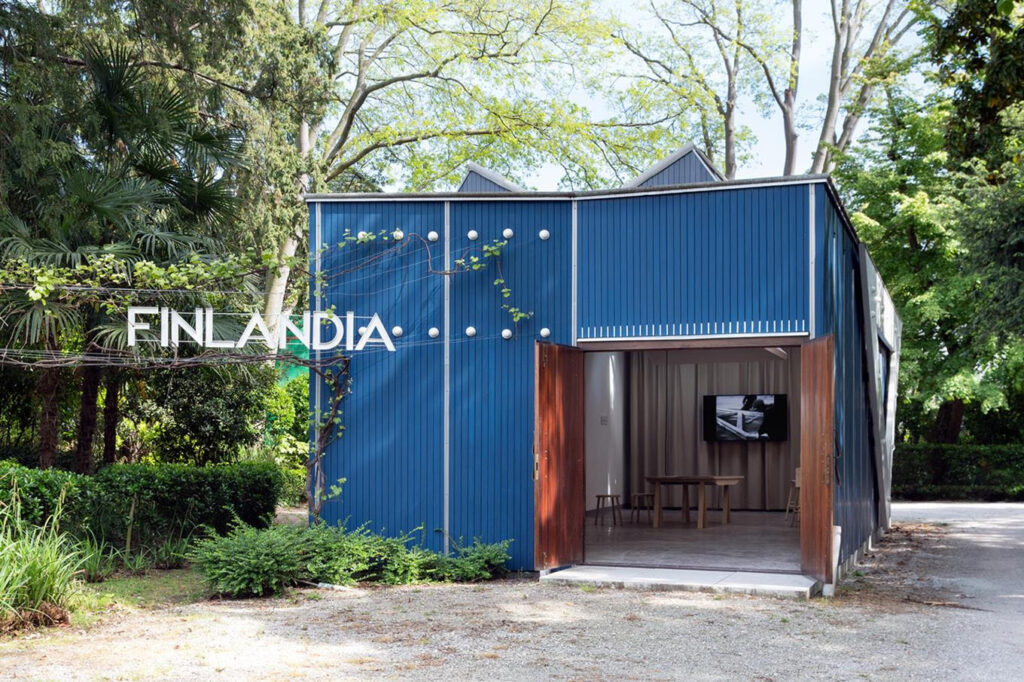 """A pavilion with blue walls. The door is open to the exhibition. On the lef side of the pavilion, there is a text """"Finlandia"""". The weather is sunny."""