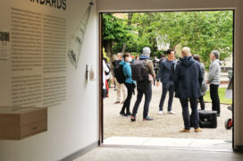 View from inside a pavilion, group of people standing outside the open door