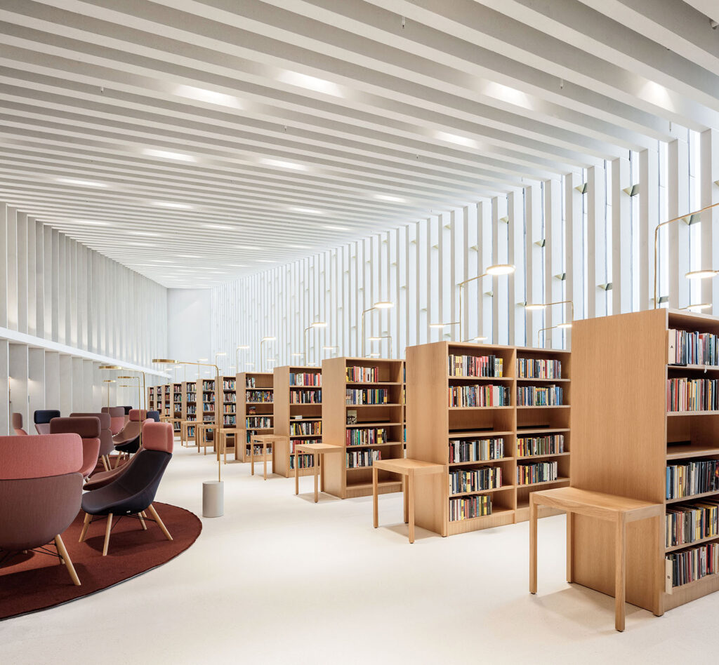 White space with vertical battens in the window wall and joists, wooden bookshelves, burgundy-coloured armchairs