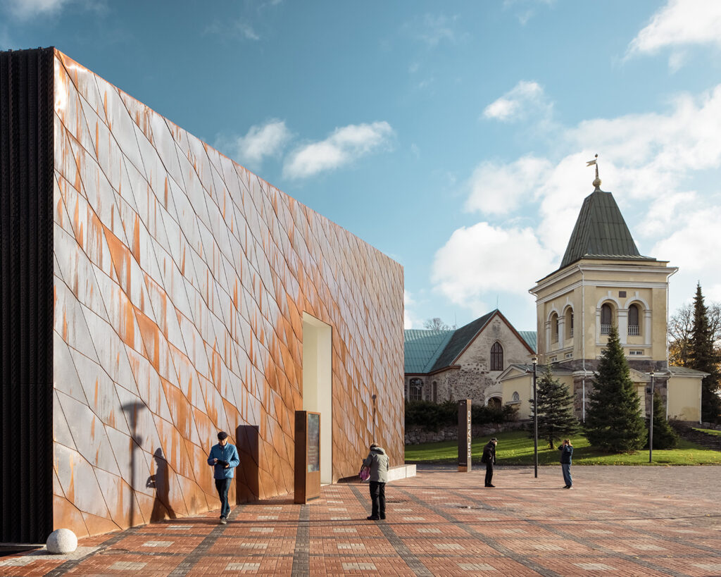 Closed copper facade with an opening in the middle standing on a paved square, medieval church and belfry in the background