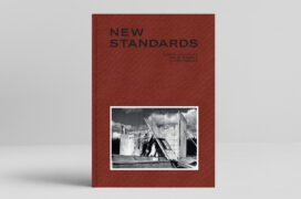 """Cover of a book, tile-red canvas with title """"New Standards"""", below a black-and-white photo of men erecting a timber wall element"""