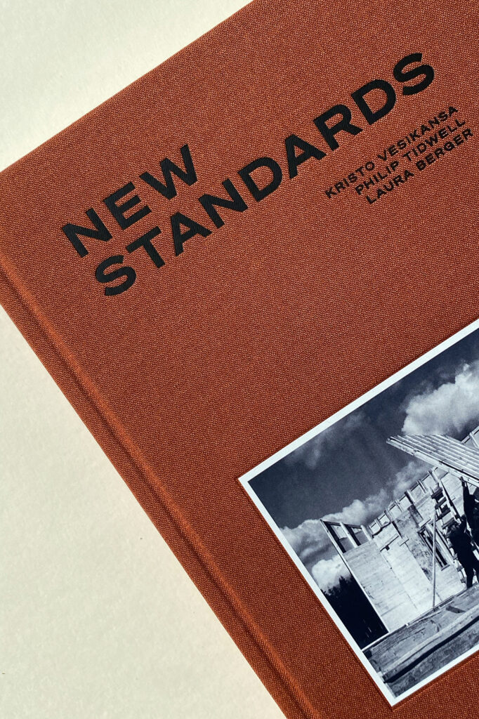 """Close-up of a book cover with brick-coloured canvas, text """"New Standards"""" and a black-and-white photo partly seen."""