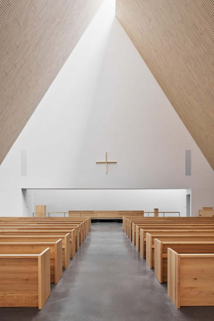 Frontal view towards altar, wooden benches and ceiling, white back wall with a delicate wooden cross