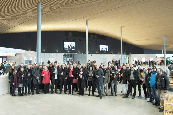 Big group of people looking at the camera in a space with an arched wooden ceiling and thin steel pillars